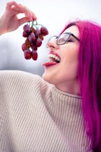 Woman eating red grapes